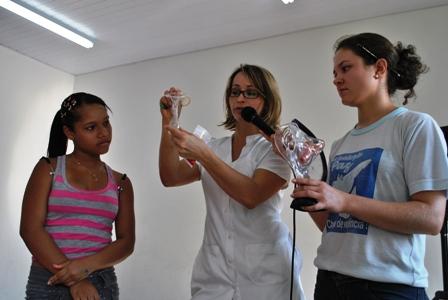 A estudante Carolaine Rodrigues recebendo orientações sobre preservativo masculino e feminino