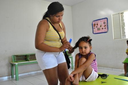 Aluna do Ponto de Cultura Pixaim (CUFA-MT) trançando o cabelo de criança atendida pela Creche Municipal