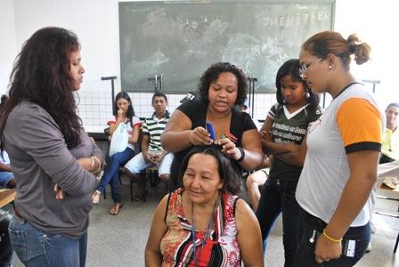 Katiane Rodrigues orientando participantes da oficina de trança afro