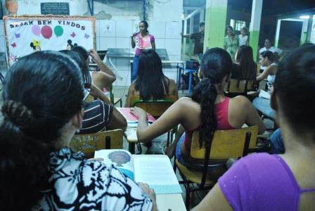 """Neusa Baptista uma das coordenadoras do Projeto Pixaim (CUFA-MT) apresentando seu  livro """"Cabelo Ruim ?"""" aos alunos"""