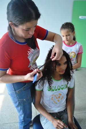 Rejane Souza Rodrigues trançando o cabelo de Naiara Gonçalves na oficina de trança no CECC