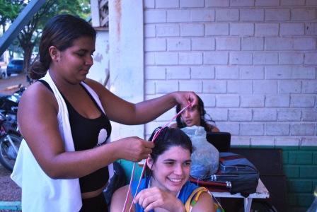 Lorraine Costa trançadeira formada nas oficinas do Ponto de Cultura Pixaim (CUFA-MT) trançando o cabelo de uma jovem