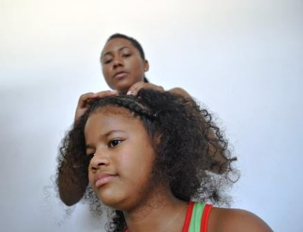 Tatiane Amorim trançando o cabelo da pequena Yara Grabriele