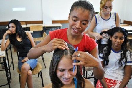 Adolescente aprendendo a arte de trançar em oficina da Caravana Pixaim
