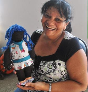 Dona Lindaura Alves exibindo a boneca negra que já confeccionou nas oficinas