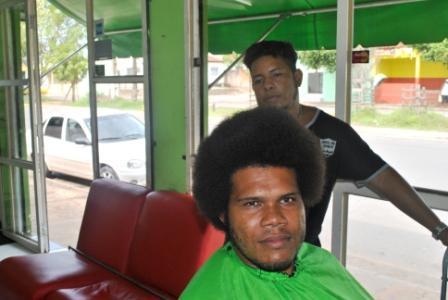 Ederson Fernandes (sentado) em início da lapidação do seu cabelo por Jair Vips (em pé)