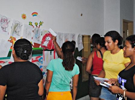 Pais observando o trabalho de seus filhos no Varal da Criatividade,confeccionado pela equipe do projeto